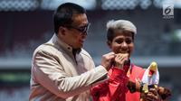 Atlet lompat jauh Indonesia, Rica Oktavia (kanan) foto bersama Menpora Imam Nahrawi usai meraih medali emas Asian Para Games 2018 di SUGBK, Jakarta, Senin (8/10). Rica menorehkan lompatan mencapai 5,25 meter. (Bola.com/Vitalis Yogi Trisna)