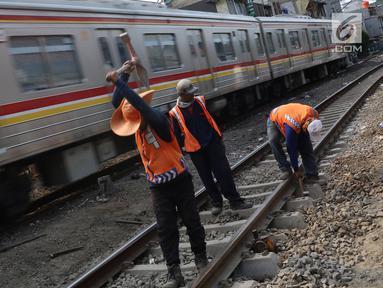 Pekerja menambahkan kerikil pada bantalan rel kereta di kawasan Roxy, Jakarta, Selasa (7/1). Penambahan kerikil tersebut dilakukan sebagai bentuk perawatan rutin agar perjalanan kereta tetap aman dan lancar. (Liputan6.com/Immanuel Antonius)