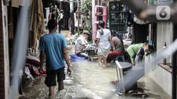Warga beraktivitas di tengah banjir yang merendam permukiman warga di Kemang Timur XI, Jakarta, Minggu (21/2/2021). Warga berharap pemerintah segera memperbaiki longsor agar banjir tidak berkepanjangan. (merdeka.com/Iqbal S. Nugroho)