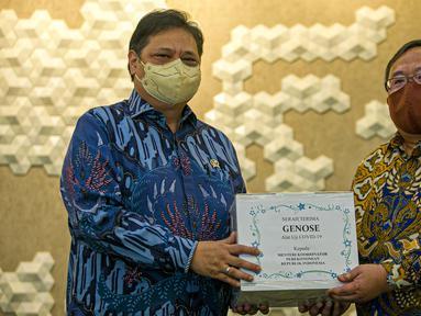 Menristek Bambang Brodjonegoro (kanan) memberikan GeNose C19 kepada Menko Bidang Perekonomian Airlangga Hartarto di Gedung Kemenko Perekonomian, Jakarta, Senin (22/3/2021). GeNose C19 diharapkan dapat semakin dikenal dan dimanfaatkan secara lebih masif. (Liputan6.com/Faizal Fanani)