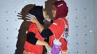 Peraih medali emas Indonesia Susanti Rahayu Aries berpelukan dengan peraih medali perak Puji Lestari usai pertandingan panjat tebing wanita Asian Games 2018 di Palembang (23/8). (AFP PHOTO / Adek Berry)