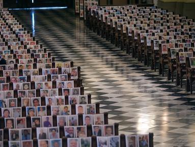 Seorang perempuan duduk di antara potret korban meninggal akibat virus corona di dalam Katedral, di Lima, Peru pada 13 Juni 2020. Misa Minggu di Katedral Lima dihadiri lebih dari 4.000 potret mereka yang telah meninggal dalam pandemi Covid-19 yang menyebar di Peru. (AP Photo/Rodrigo Abd)