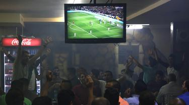 Warga Palestina menonton laga El Clasico antara Barcelona melawan Real Madrid di West Bank City, Ramallah, Minggu (6/5/2018). Konflik perang tak menyurutkan fenomena El Clasico. (AFP/Abbas Momani)