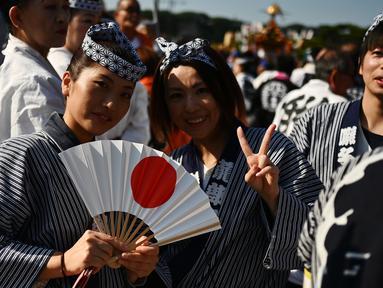 Dua wanita berpose saat mengikuti perayaan nasional untuk menandai penobatan Kaisar Jepang Naruhito di depan Istana Kekaisaran di Tokyo (9/11/2019). Kaisar Naruhito menjalankan ritual penobatannya setelah dilantik pada 1 Mei 2019. (AFP Photo/Charly Triballeau)
