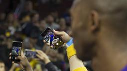 Fans melakukan foto selfie bersama Pemain Los Angels Lakers, Kobe Bryant #24 usai bertanding melawan Philadelphia 76ers pada laga NBA di Wells Fargo Center, Philadelphia, Pennsylvania, Selasa (1/12/2015).  (AFP Photo/Mitchell Leff/Getty Images/AFP)