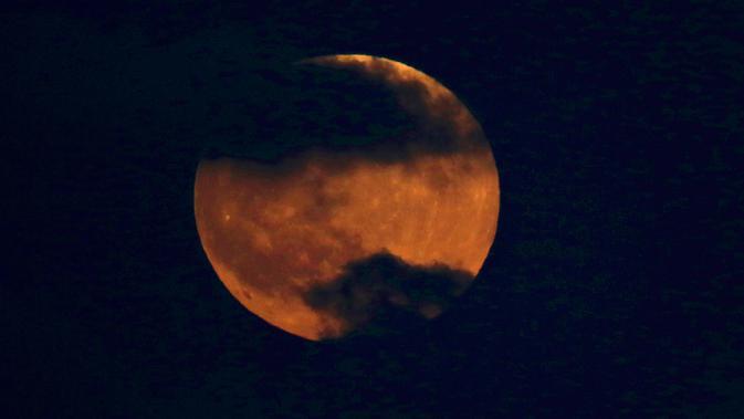 Bulan tampak berwarna merah darah saat terjadinya fenomena gerhana bulan total  di atas langit Tel Aviv, Israel,, Jumat (27/7). Gerhana bulan terlama pada abad ini dapat disaksikan di seluruh dunia dengan mata telanjang. (AP/Ariel Schalit)