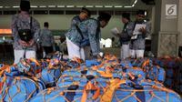 Panitia memeriksa koper para calon jemaah haji Kloter 1 di Asrama Haji Pondok Gede, Jakarta, Senin (16/7). Sebanyak 388 calon jemaah haji asal Jakarta Timur telah mulai masuk ke asrama. (Merdeka.com/Iqbal Nugroho)