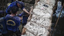 Petugas Suku Dinas SDA Jakarta Selatan membangun turap permanen di lokasi tanggul jebol di Kelurahan Jatipadang, Jakarta, Rabu (16/1). Berdasarkan keterangan warga, tanggul tersebut jebol pada Minggu, 13 Januari 2018. (Liputan6.com/Faizal Fanani)
