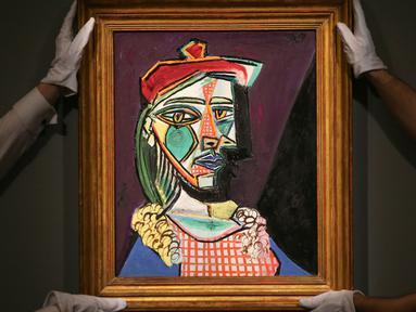 Petugas rumah lelang Sotheby menata lukisan Pablo Picasso bertema Marie-Therese Walter pada sesi pemotretan di London, Rabu (22/2). Lukisan yang akan dilelang ini diperkirakan nilainya mencapai US$ 50 juta atau Rp 685 miliar. (Daniel LEAL-OLIVAS/AFP)