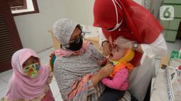 Bidan dibantu Kader Posyandu memberikan vaksin vitamin A dan imunisasi di Posyandu RW 20, Kelurahan Pondok Benda, Tangerang Selatan, Selasa (18/8/2020). Pemerintah sudah mengaktifkan pelayanan posyandu ketiga sejak pandemi Covid-19 dengan memperketat protokol kesehatan. (merdeka.com/Dwi Narwoko)