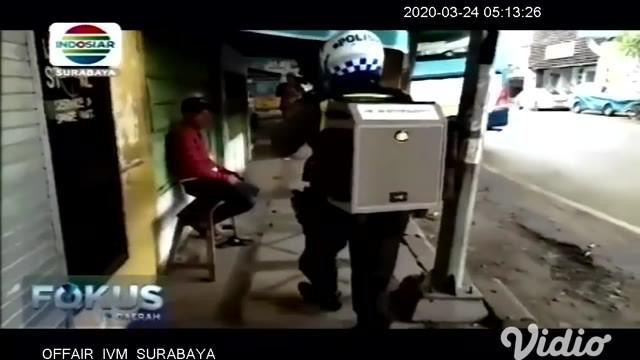 Anggota Lalu Lintas Polres Pasuruan Kota, Bripka Suwaji melakukan himbauan cegah virus Covid-19 dengan membawa megaphone ditaruh menggunakan tas besar.