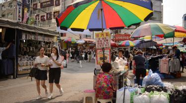Dua wanita berjalan di antara kios di pasar Namdaemun di Seoul (2/7/2019). Pasar Namdaemun atau Namdaemun Sijang adalah pasar yang terletak di Seoul, Korea Selatan. Pasar ini terletak di sebelah timur Gerbang Besar Selatan (Sungnyemun) yang bersejarah dengan luas 40.000 m². (AFP Photo/Minji Suh)