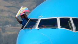 Termasuk gaya unik yang ditunjukan oleh atlet asal Ekuador Neisi Patricia Dajomes yang melakukan selebrasi di kokpit pesawat saat tiba di bandara Kota Quito, Ekuador. (Foto: AFP/Rodrigo Buendia)