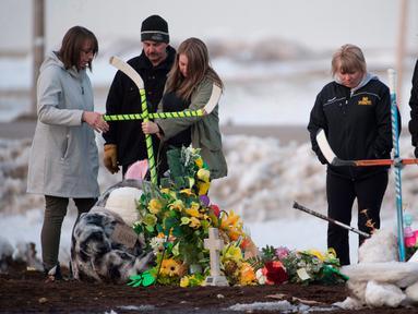 Sebuah keluarga menempatkan salib yang terbuat dari tongkat hoki untuk memberi penghormatan kepada korban kecelakaan bus yang membawa tim hoki es Humboldt Broncos di Provinsi Saskatchewan, Kanada (9/4). (Jonathan Hayward/The Canadian Press via AP)
