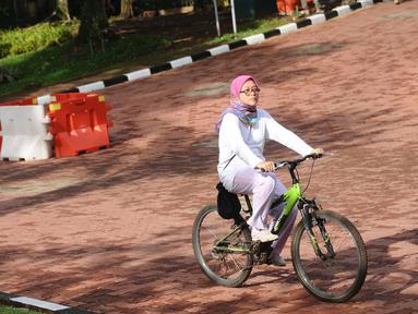 Warga bersepeda melintas di salah satu bundaran di kawasan Kebun Binatang Ragunan, Jakarta, Minggu (9/10). Kawasan KBR menjadi salah satu lokasi alternatif warga Jakarta untuk berolahraga pada Minggu pagi. (Liputan6.com/Helmi Fithriansyah)
