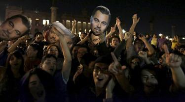 Fans memegang topeng Leonardo DiCaprio saat merayakan kemenangan sang idola sebagai Aktor Terbaik untuk film The Revenant pada ajang bergengsi Academy Awards ke-88 atau lebih dikenal Piala Oscar 2016, di Monterrey, Senin (29/2). (REUTERS/Daniel Becerril)