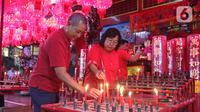 Warga keturunan Tionghoa menyalakan lilin saat sembahyang Vihara Amurva Bhumi, kawasan Karet Semanggi, Jakarta, Jumat (24/1/2020) malam. Ibadah tersebut dalam rangka menyambut Tahun Baru Imlek 2571/2020. (Liputan6.com/Herman Zakharia)