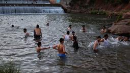 Orang-orang mendinginkan diri dalam aliran air ketika suhu mencapai 40 derajat celsius di Islamabad, Pakistan pada Rabu (27/5/2020). Banyak kota di Pakistan menghadapi kondisi gelombang panas dengan suhu mencapai 50 derajat celsius di beberapa tempat.  (AP Photo/Anjum Naveed)