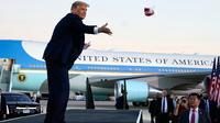 Presiden Donald Trump melemparkan masker dari atas panggung ke kerumunan pendukung saat berkampanye di Bandara Internasional Orlando Sanford di Sanford, Florida, Senin (12/10/2020). Donald Trump kembali berkampanye untuk pertama kalinya sejak dia mengumumkan diagnosis COVID-19. (AP Photo/Evan Vucci)