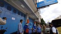 Petugas Dinkes Kota Cirebon menutup toko alkes dari usaha grup apotek Pasuketan karena belasan pegawai farmasi terkonfirmasi positif covid-19. Foto (Liputan6.com / Panji Prayitno)