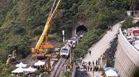 Petugas penyelamat memindahkan bagian dari kereta yang tergelincir dekat Ngarai Taroko di Hualien, Taiwan, Sabtu (3/4/2021). Kereta delapan gerbong yang berisi 494 orang itu berangkat dari Taipei menuju Taitung saat kecelakaan. (AP Photo/Chiang Ying-ying)