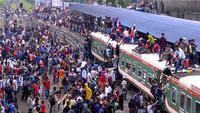 Ratusan orang berupaya menaiki atap kereta api untuk menuju kampung halaman di Dhaka, Bangladesh pada 4 Juni 2019. Pemadangan mencengangkan dari ratusan yang naik dan duduk di atas kereta karena gerbong yang penuh terlihat pada menjelang Idul Fitri di Bangladesh. (MUNIR UZ ZAMAN/AFP)