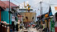 KM Sabuk Nusantara 39 terdampar di antara rumah warga setelah tsunami melanda Palu dan Donggala, Sulawesi Tengah, Selasa (2/10). Berdasarkan data di marinetraffic.com, KM Sabuk Nusantara 39 memiliki bobot mati 500 ton. (AP Photo/Tatan Syuflana)