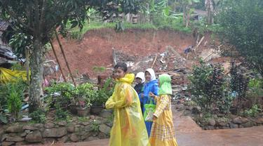 Sejumlah bocah warga Dusun Jatiluhur, Padangjaya, Majenang, Cilacap, pulang mengaji melewati rumah yang ambruk akibat longsor, awal 2018. (Foto: Liputan6.com/Muhamad Ridlo)