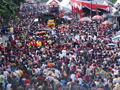 Warga memadati ruas Jalan Gajah Mada, Jakarta untuk menyaksikan karnaval Cap Go Meh 2018, Minggu (4/3). Beragam atraksi budaya ditampilkan dalam karnaval perayaan Cap Go Meh 2018 di kawasan Glodok Jakarta. (Liputan6.com/Helmi Fithriansyah)