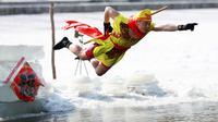Seorang pria saat melompat ke danau yang beku di Shenyang di provinsi Liaoning, China timur laut (2/3). (AFP Photo)