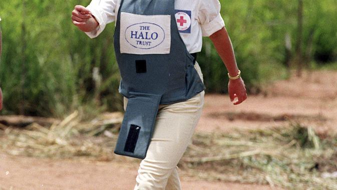 Mendiang Putri Diana mengenakan masker tersenyum saat berjalan di tengah-tengah ladang ranjau Huambo, Angola, 15 Januari 1997. (John Stillwell/PA via AP, File)