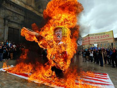 Para pengunjuk rasa membakar patung karakter Presiden AS Donald Trump saat melakukan aksi protes pada peringatan Hari Buruh di Bogota, Kolombia (1/5). Warga Kolombia merayakan Hari Buruh dengan membakan patung Donald Trump. (AP/Fernando Vergara)