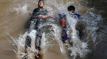 Anak-anak muda mendinginkan diri dalam aliran kanal sungai saat suhu mencapai 40 derajat celsius di Lahore, Pakistan pada Rabu (27/5/2020). Banyak kota di Pakistan menghadapi kondisi gelombang panas dengan suhu mencapai 50 derajat celsius di beberapa tempat.  (Photo by Arif ALI / AFP)