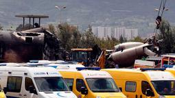 Mobil tim medis dan ambulans berada di dekat reruntuhan pesawat tentara Aljazair yang jatuh di Aljazair (11/4). Pejabat setempat mengatakan pesawat jatuh tak lama setelah lepas landas dari pangkalan udara Boufarik. (AP Photo/Anis Belghoul)