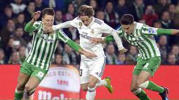 Luka Modric mencoba melewati hadangan pemain Real Betis pada laga lanjutan La Liga Spanyol yang berlangsung di stadion Benito Villamarin, Senin (14/1). Real Madrid menang 2-1 atas Real Betis. (AFP/Cristina Quicler)