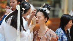 """Peserta merias wajahnya sebelum ambil bagian dalam peragaan busana """"hanfu"""", pakaian tradisional khas China di kota Shenyang, China timur laut pada Minggu (15/9/2019). Hanfu sendiri sebenarnya adalah baju tradisional Cina yang digunakan etnis Han China. (Photo by STR / AFP)"""