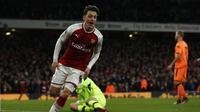 Gelandang Arsenal, Mesut Ozil, mengalami cedera lutut dan diprediksi bakal absen ketika menghadapi Chelsea di Emirates Stadium pada Rabu (3/1/2018). (AFP/Adrian Dennis)