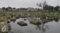 Suasana TPU Tanah Kusir yang terendam banjir, Jakarta Selatan, Jumat (26/8). Warga memanfaatkan Banjir yang merendam makam di kawasan tanah kusir ini terjadi akibat luapan Sungai Pesanggrahan. (Liputan6.com/Johan Tallo)