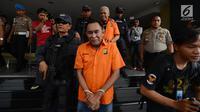 Polisi bersenjata menggiring tersangka dugaan pengaturan skor di Polda Metro Jaya, Jakarta, Rabu (10/4). Sebelum diserahkan ke kejaksaan, polisi lebih dulu mengecek kesehatan para tersangka di Biddokes Polda Metro Jaya. (merdeka.com/Imam Buhori)