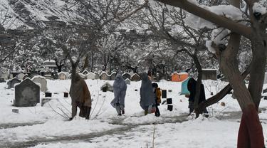 Sejumlah orang berjalan melewati makam usai hujan salju lebat di Quetta, Pakistan, Senin (13/1/2020). Cuaca buruk berupa hujan salju lebat, hujan, dan banjir bandang melanda Pakistan dan Afghanistan. (Banaras KHAN/AFP)