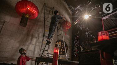 Pekerja memasang lampu lampion di lingkungan Vihara Tanda Bhakti di kawasan Petak Sembilan, Glodok, Jakarta, Rabu (3/2/2021). Bersih-bersih Rumah Ibadah dilakukan untuk menyambut Hari Raya Imlek yang jatuh pada 12 Februari 2021. (Liputan6.com/Faizal Fanani)