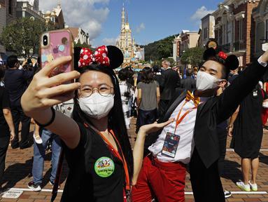 Para pengunjung yang mengenakan masker untuk mencegah penyebaran COVID-19 berswafoto di Disneyland Hong Kong, Kamis (18/6/2020). Disneyland Hong Kong kembali beroperasi pada 18 Juni 2020 dengan menerapkan sejumlah protokol kesehatan baru. (AP Photo/Kin Cheung)