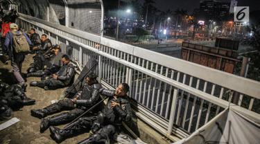 Aparat kepolisan melepas lelah di jembatan penyeberangan orang (JPO) depan Gedung DPR, Jakarta, Selasa (24/9/2019). Mereka melepas lelah usai mengawal demonstrasi mahasiswa menolak pengesahan RUU KUHP dan revisi UU KPK. (Liputan6.com/Faizal Fanani)