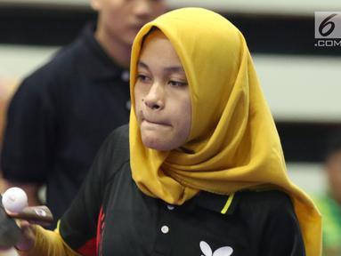 Petenis meja difabel Indonesia, Leli Marlina melakukan serve saat melawan Bee Tin Toh (Singapura) pada Indonesia Para Games Invitational Tournament 2018 di GBK Arena, Jakarta, Minggu (1/7). Leli unggul tiga set langsung. (Liputan6.com/Helmi Fithriansyah)