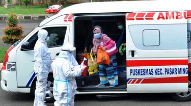 Pasien orang tanpa gejala (OTG) Covid-19 turun dari ambulance untuk selanjutnya dirawat selama 14 hari di Graha Wisata Ragunan, Jakarta, (21/12/2020). Hari ini terjadi penambahan 22 pasien OTG dari wilayah Sudinkes Jaksel sehingga total yang dirawat 34 pasien OTG. (merdeka.com/Arie Basuki)