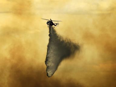 Helikopter menjatuhkan tembakan pada api yang terbakar di dekat Evergreen, Colo (13/7/2020). Cuaca dingin dan hujan yang turun memberikan harapan kepada petugas pemadam kebakaran untuk dapat mengendalikan api yang menyebabkan kebakaran di wilayah tersebut. (RJ Sangosti/The Denver Post via AP)