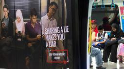 Iklan larangan penyebaran hoax atau berita bohong terpasang pada kereta di Stasiun Kereta Kuala Lumpur, Malaysia, Kamis (29/3). Penyebar hoax bakal dikenai hukuman enam tahun penjara. (AP Photo/Vincent Thian)