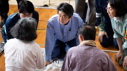 Perdana Menteri Jepang Shinzo Abe mengunjungi lokasi penampungan korban banjir di Mabi, Prefektur Okayama, Rabu (11/7). Sebelumnya, Abe sudah membatalkan rencana perjalanan luar negeri karena bencana yang kian memburuk. (AFP/Martin BUREAU)