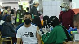 Warga mendapatkan vaksin Covid-19 di Gelanggang Olahraga (GOR) Ciracas, Jakarta Timur, Kamis (24/6/2021). GOR Ciracas resmi ditunjuk menjadi sentra vaksinasi Covid-19 untuk kelompok usia 18-50 tahun di wilayah Jakarta Timur. (Liputan6.com/Herman Zakharia)