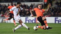 Winger AS Roma, Justin Kluivert, menendang bola ke gawang dibayangi pemain Istanbul Basaksehir pada laga kelima Grup J Liga Europa 2019-2020 di stadion Fatih Terim, Kamis (28/11/2019). AS Roma menang meyakinkan dengan skor 3-0.  (Ozan KOSE / AFP)
